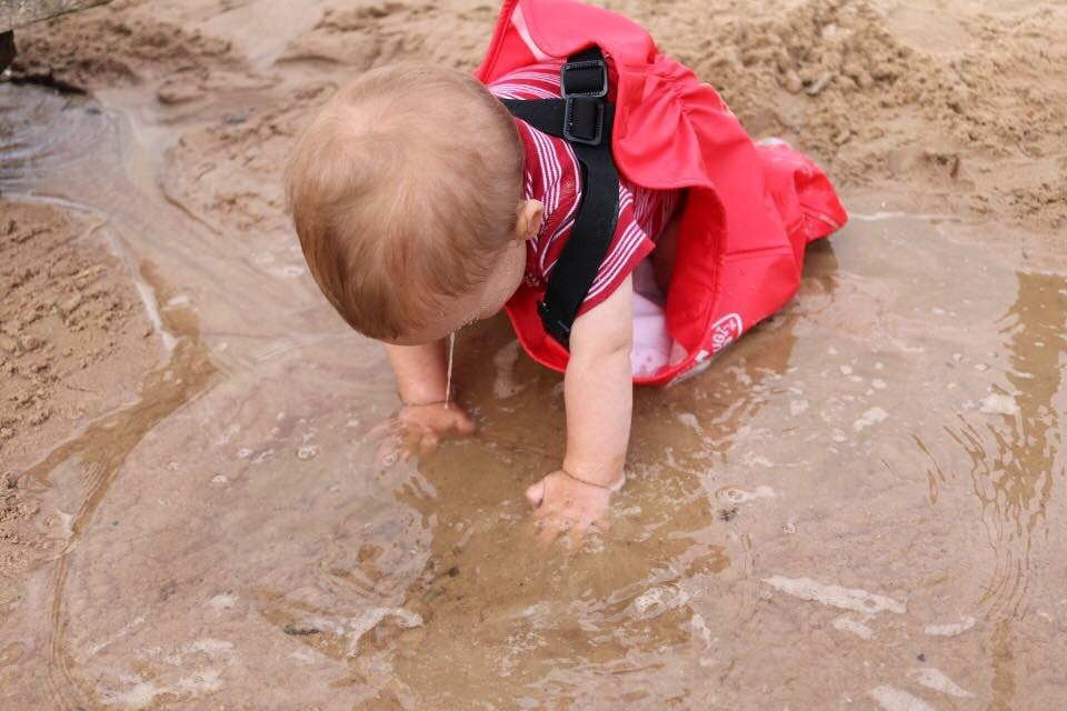Baby playing in water sand at web adventure park in York